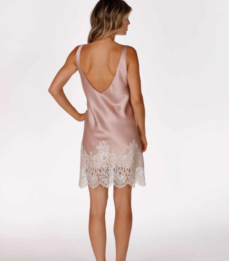 A silk pink chemise with white lace is worn by a women