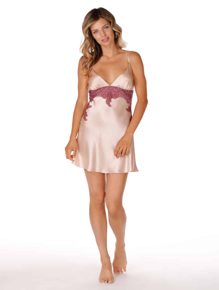 silk pink chemise with lace is worn by women posed with head tilted and leg slightly raised