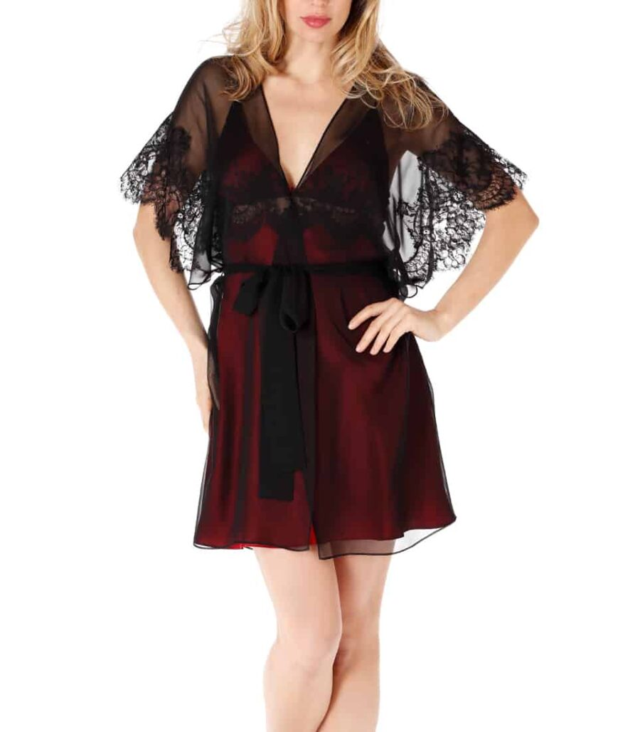 A silk chiffon black short robe with black lace is paired with a silk red chemise worn by a women
