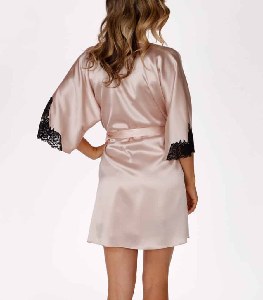 A silk pink short robe with black lace is worn by a women