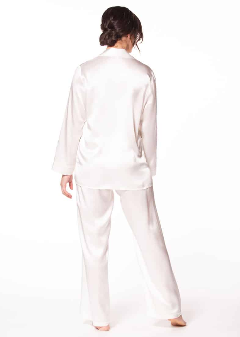 A white silk pajama set is being worn by a women