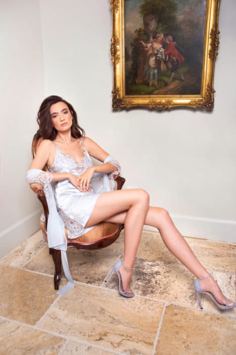 A silk blue chemise with blue lace is worn by a women sitting on a chair.