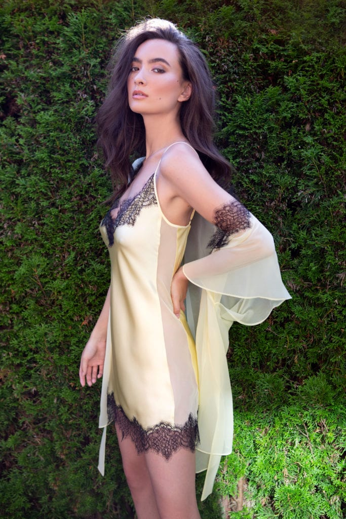 A silk yellow chemise with black lace paired with a yellow silk chiffon short robe with lace is worn by a women.