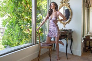 A silk chemise with our Arabella floral print is worn by a women looking out a large window