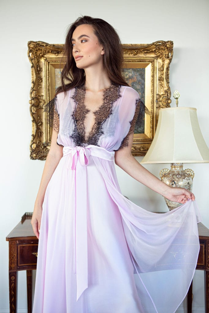 A silk pink chiffon robe with black lace is worn by a women