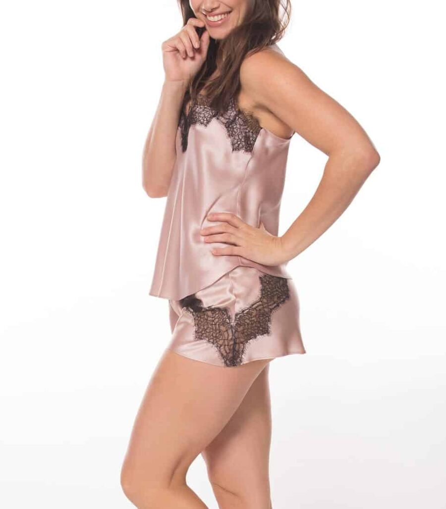 silk pink camisole and short set with black lace is worn by a women