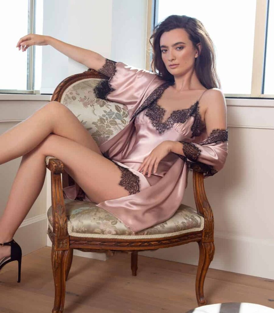 silk pink robe with black lace is paired with a pink chemise with black lace is worn by a women