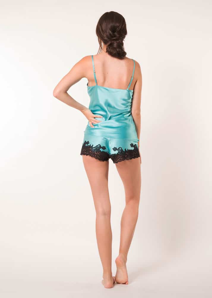 A blue silk cami and tap set with black lace is worn by a women