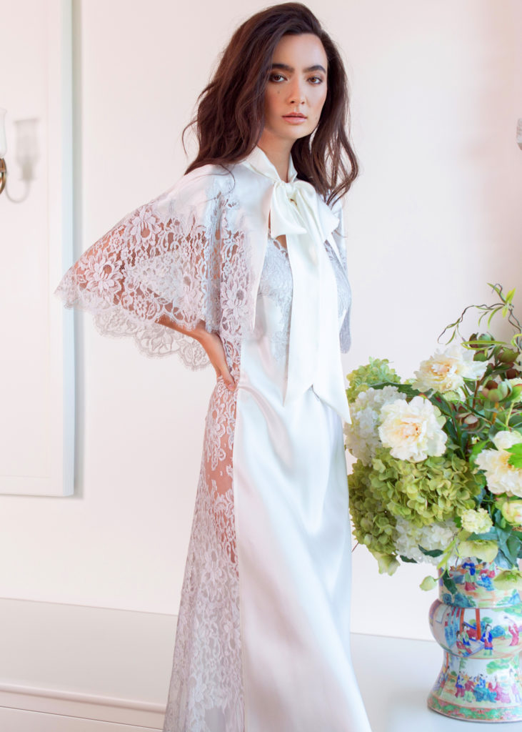 A silk white cape with white lace paired with a silk white gown with lace is worn by a women