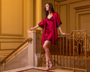 A silk red chemise with black lace paired with a matching silk short robe with black lace is worn by a women