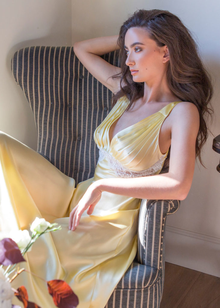 A silk yellow silk gown with white lace is worn by a women